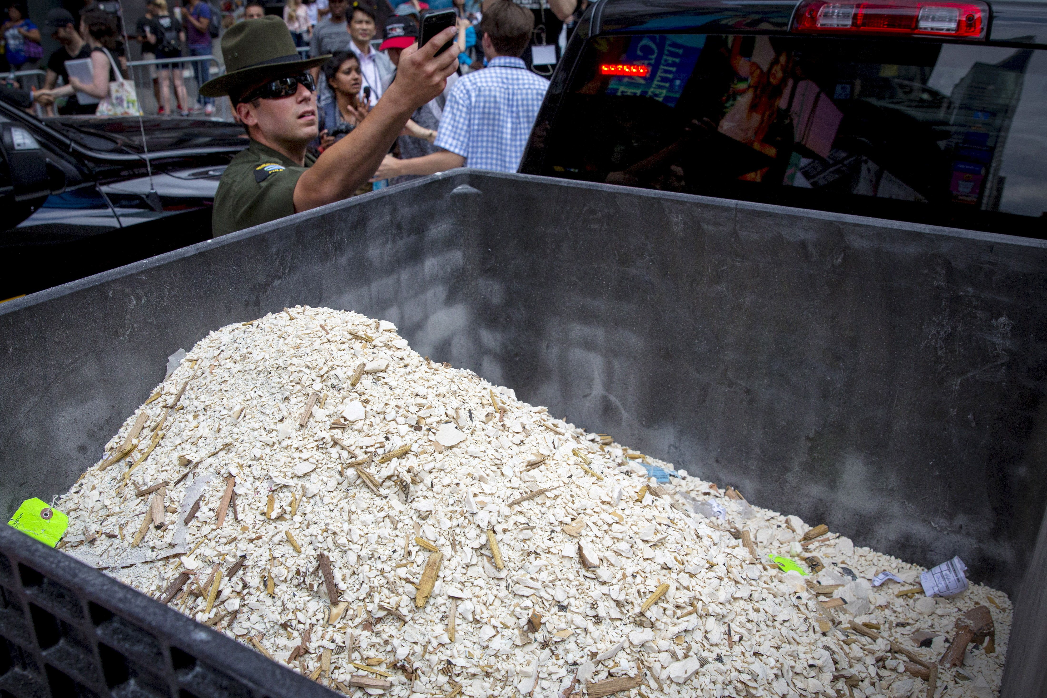 A New York State Department of Environmental Conservation enforcement officer photographs crushed pieces of confiscated ivory in New York's Times Square June 19, 2015. More than a ton of ivory confiscated from New York and Philadelphia was crushed in Times Square on Friday to show intolerance for elephant poaching and the illegal ivory trade, federal wildlife authorities said.  REUTERS/Brendan McDermid
