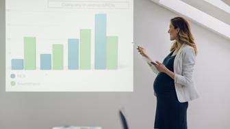 Smiling Pregnant Woman Holding digital tablet and giving presentation in office. Pointing to chart with pencil.