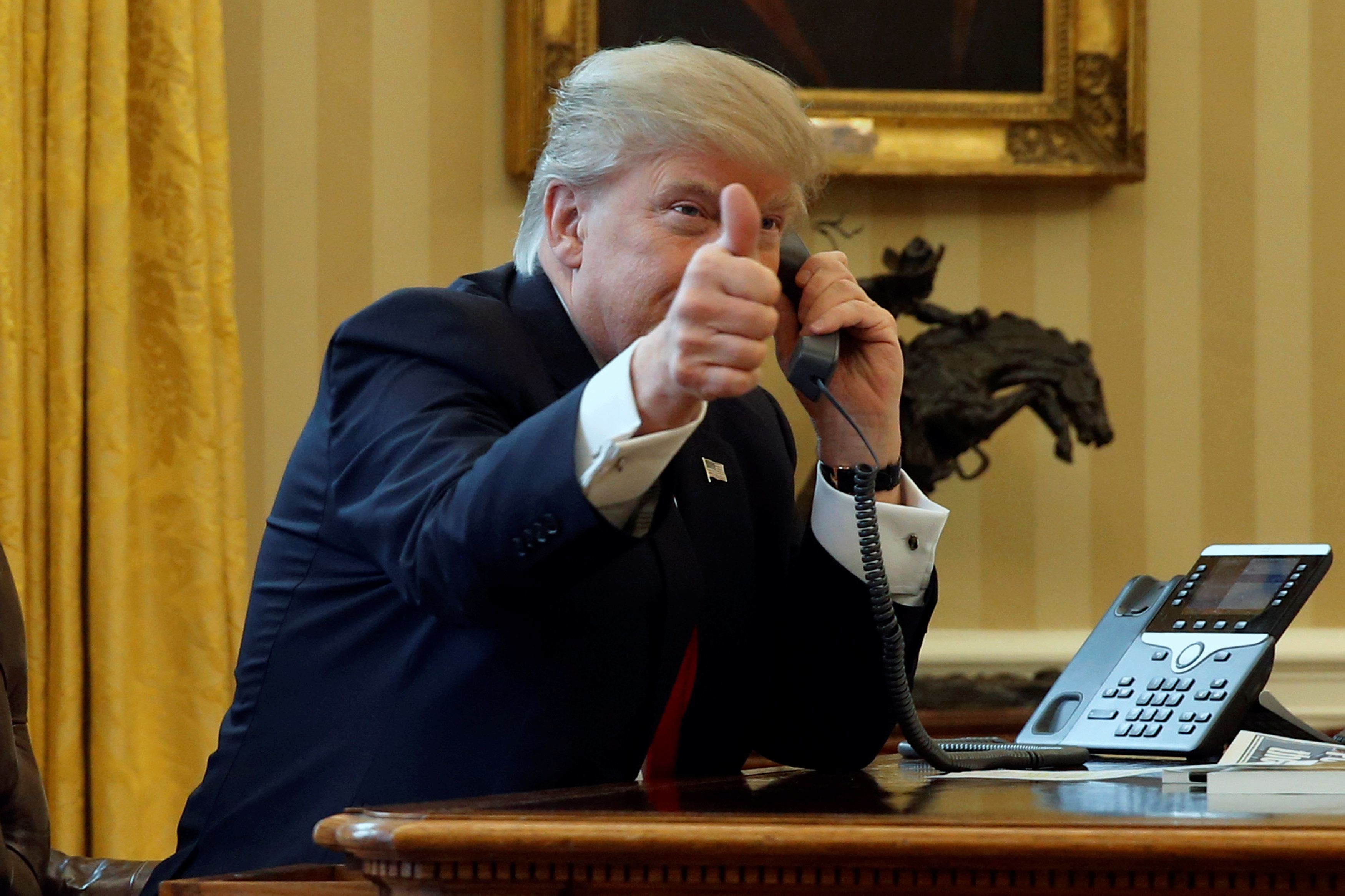 U.S. President Donald Trump gives a thumbs-up to reporters as he waits to speak by phone with the Saudi Arabia's King Salman in the Oval Office at the White House in Washington, U.S. January 29, 2017. REUTERS/Jonathan Ernst