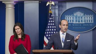 Stephen Miller, White House senior advisor for policy, speaks as Sarah Huckabee Sanders, White House press secretary, left, listens during a White House press briefing in Washington, D.C., U.S., on Wednesday, Aug. 2, 2017. President Donald Trump endorsed new legislation that would reduce legal immigration to the U.S. and evaluate visa applications based on merit, with a preference for people with higher education or job skills. Photographer: Zach Gibson/Bloomberg via Getty Images