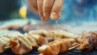 Closeup of unrecognizable male chef seasoning meat on a grill with a pinch of salt. Very shallow focus.