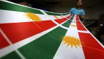 An Iraqi man prints a flag of Kurdistan, in Arbil, the capital of the autonomous Kurdish region of northern Iraq, on June 8, 2017. Iraq's autonomous Kurdish region will hold a historic referendum on statehood in September, despite opposition to independence from Baghdad and possibly beyond.  / AFP PHOTO / SAFIN HAMED        (Photo credit should read SAFIN HAMED/AFP/Getty Images)