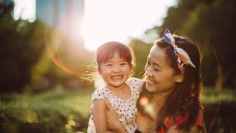 Pretty young mom carrying the lovely toddler girl talking and smiling joyfully with her in the park
