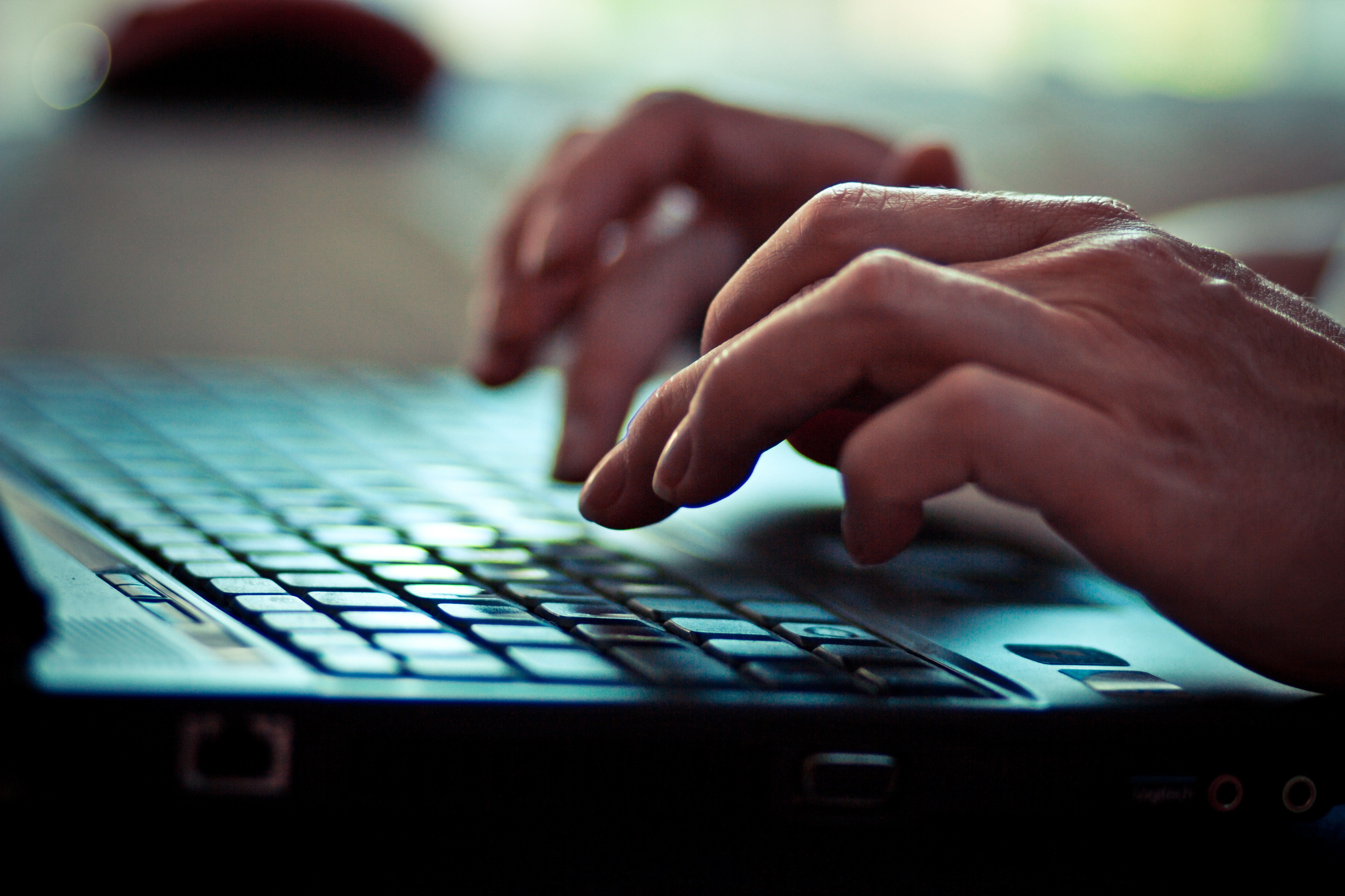 Women is writing on laptop keyboard.