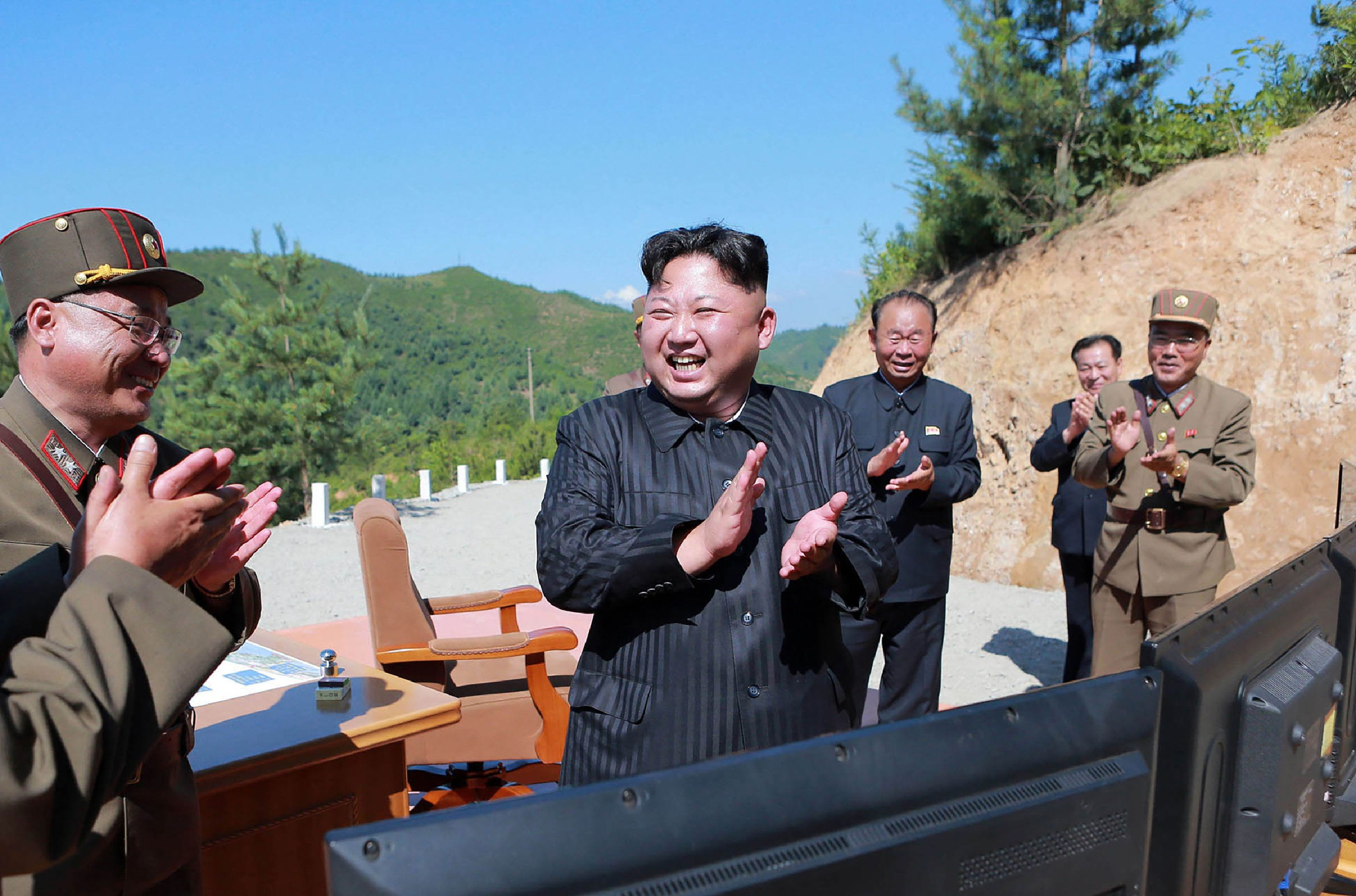 This picture taken on July 4, 2017 and released by North Korea's official Korean Central News Agency (KCNA) on July 5, 2017 shows North Korean leader Kim Jong-Un (C) celebrating the successful test-fire of the intercontinental ballistic missile Hwasong-14 at an undisclosed location. South Korea and the United States fired off missiles on July 5 simulating a precision strike against North Korea's leadership, in response to a landmark ICBM test described by Kim Jong-Un as a gift to 'American bastards'. / AFP PHOTO / KCNA VIA KNS / STR / South Korea OUT / REPUBLIC OF KOREA OUT   ---EDITORS NOTE--- RESTRICTED TO EDITORIAL USE - MANDATORY CREDIT 'AFP PHOTO/KCNA VIA KNS' - NO MARKETING NO ADVERTISING CAMPAIGNS - DISTRIBUTED AS A SERVICE TO CLIENTS THIS PICTURE WAS MADE AVAILABLE BY A THIRD PARTY. AFP CAN NOT INDEPENDENTLY VERIFY THE AUTHENTICITY, LOCATION, DATE AND CONTENT OF THIS IMAGE. THIS PHOTO IS DISTRIBUTED EXACTLY AS RECEIVED BY AFP.    /         (Photo credit should read STR/AFP/Getty Images)