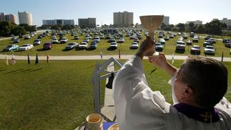 DAYTONA BEACH, FL - MARCH 28:  Rev. Larry Deitch holds aloft a goblet of wine during service at the Daytona Beach Drive-In Christian Church March 28, 2004 in Daytona Beach, Florida. Every Sunday on the 11.75-acre lot, where the former Neptune Drive-In theater stood, the Word is delivered via radio signal and speaker to people listening in parked cars and trucks. The drive-in church, one of only a few across the nation opened 51 years ago as a way to draw tourists in for prayer between sunning at the beach or other distractions during a vacation.  (Photo by Joe Raedle/Getty Images)