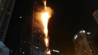 Flames shoot up the sides of the Torch tower residential building in the Marina district, Dubai, United Arab Emirates, in this August 4, 2017 picture by Mitch Williams. Mitch Williams/Social Media Website/via REUTERS     ATTENTION EDITORS - THIS IMAGE WAS PROVIDED BY A THIRD PARTY. NO ARCHIVES. NO RESALES. MANDATORY ON-SCREEN CREDIT: Mitch Williams / @MitchGWilliams THIS PICTURE WAS PROCESSED BY REUTERS TO ENHANCE QUALITY. AN UNPROCESSED VERSION HAS BEEN PROVIDED SEPARATELY.