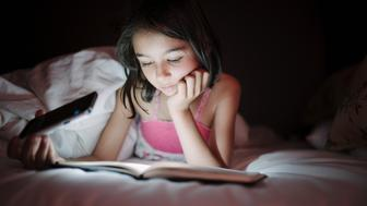 Mixed race girl reading by cell phone light in bed