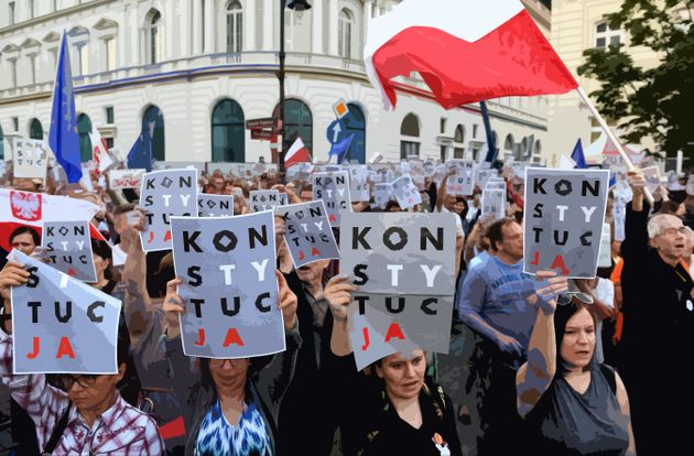 Demonstrators in Poland hold posters reading