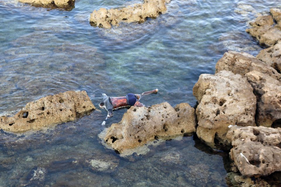 The dead body of a migrant that washed ashore is seen on the coast of Tajoura, east of Tripoli, Libya...