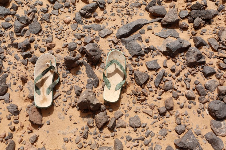 A pair of flip flops, which were left behind by a migrant, lie on the ground in the desert near the border...