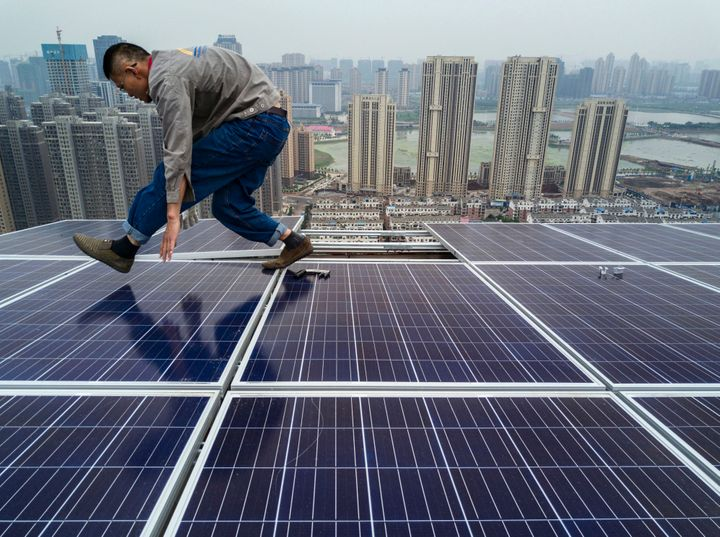 A Chinese worker installing solar panels on the roof of a new building in Wuhan on May 15.