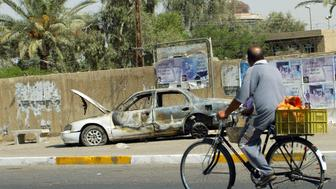 An Iraqi man rides a bicycle passing by a remains of a car in Baghdad, 20 September 2007. The car was burnt during the incident  when Blackwater guards escorting US embassy officials opened fire in a Baghdad neighbourhood, 16 September 2007, killing 10 people and wounding 13.  Iraq and the United States agreed to establish a joint commission to examine security of US-government civilians in Iraq following a deadly shooting involving private security firm Blackwater, State Department spokesman Tom Casey said.     AFP PHOTO/ ALI YUSSEF (Photo credit should read ALI YUSSEF/AFP/Getty Images)