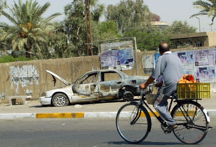 An Iraqi man rides a bicycle passing by a remains of a car in Baghdad, 20 September 2007.The car was burnt during the i