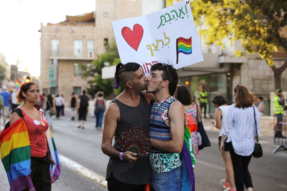 Participants kiss during a march in Jerusalem's 16th Gay Pride Parade August 3, 2017.