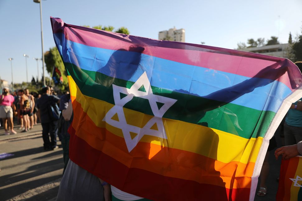 Participants hold a flag as they march in Jerusalem's 16th Gay Pride Parade August 3, 2017.
