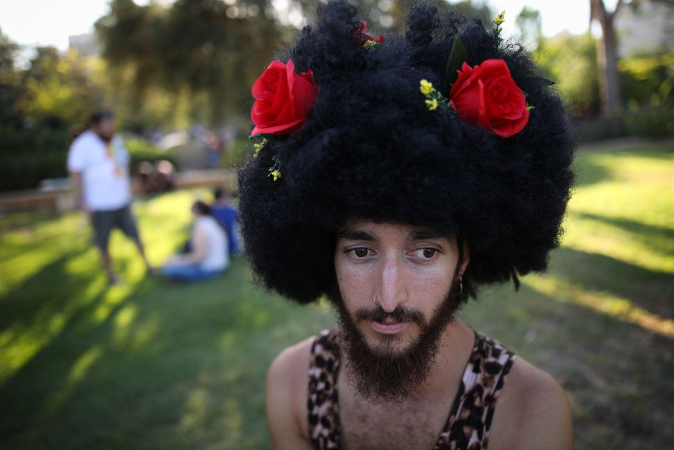 A young man wearing a dress and an Afro wig takes part in the annual Gay Pride parade.