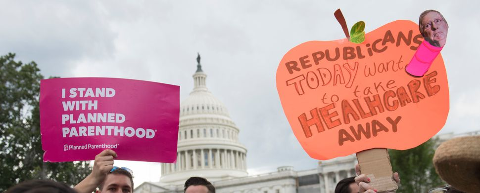Supporters of Planned Parenthood hold a rally as they protest the US Senate Republicans' healthcare bill outside the US Capit
