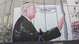 BETHLEHEM, WEST BANK - AUGUST 4 :  People walk by graffiti art depicting US President Donald J. Trump on Israeli separation barrier in the West Bank town of Bethlehem on August 04, 2017.  (Photo by Issam Rimawi/Anadolu Agency/Getty Images)