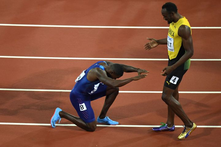After winning the 100-meter dash, Justin Gatlin kneels in front of Jamaica's Usain Bolt after Gatlin won the final of the men