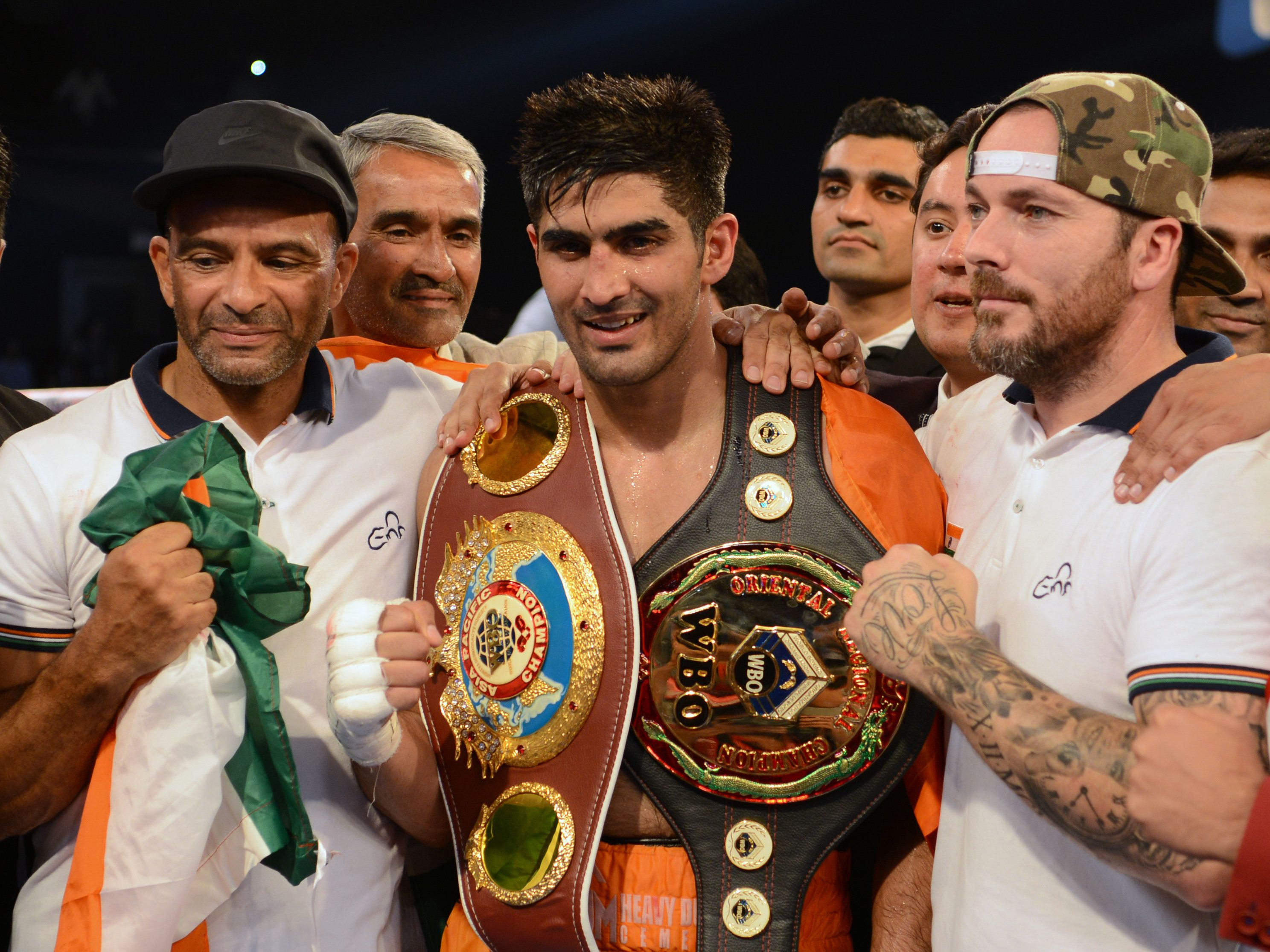 Indian boxer Vijender Singh celebrates after winning the double title bout against China's Zulpikar Maimaitiali in Mumbai on