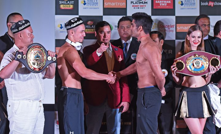 China's Zulpikar Maimaitiali (left) and India's Vijender Singh (right) shake hands during the official weigh-in on Friday bef