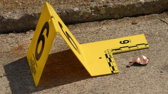 An evidence marker placed next to a metal fragment from a bullet that landed on the west side of Reisterstown Road, across the street from  where a baby girl was found in a car surrounded by more bullet fragments on March 27, 2017 in Balitmore, Md. (Amy Davis/Baltimore Sun/TNS via Getty Images)