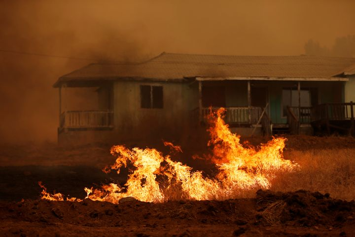 Grass burns in front of a home during the Detwiler fire in California, on July 19.