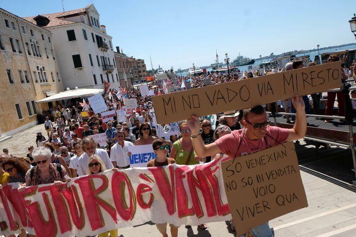 "A resident holds a placard ""I don't want to go, i'm staying"" during a protest in Venice, Italy, July 2, 2017."