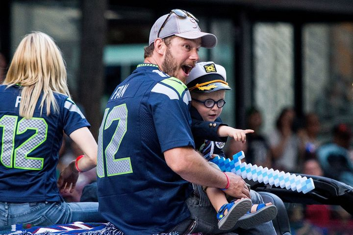 Chris Pratt and son Jack Pratt ride in the Seafair Torchlight Parade.