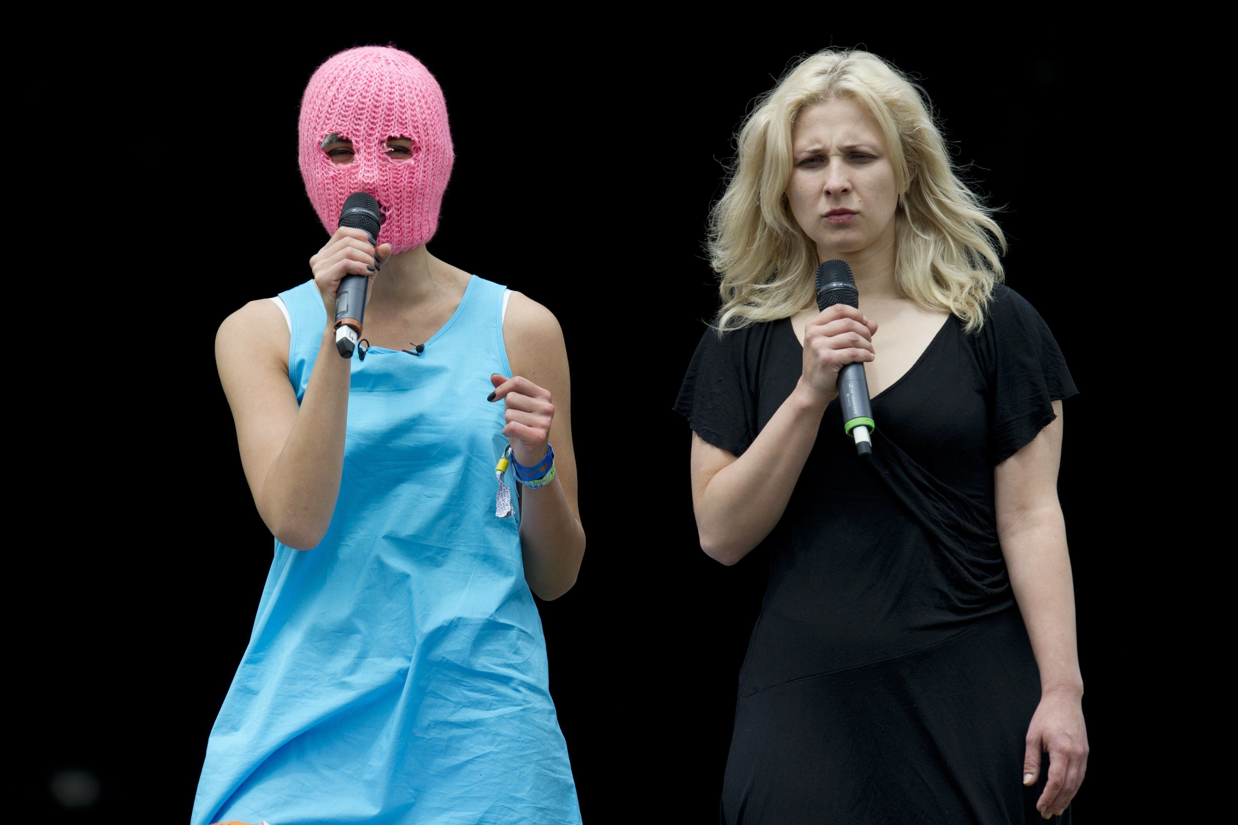 Russian activists Nadezhda Tolokonnikova (L) and Maria Alyokhina and members of Russian feminist punk rock protest group Pussy Riot address the crowd from on top of a Russian military vehicle at The Park stage on the first official day of the Glastonbury Festival of Music and Performing Arts on Worthy Farm near the village of Pilton in Somerset, South West England, on June 26, 2015.    AFP PHOTO / OLI SCARFF        (Photo credit should read OLI SCARFF/AFP/Getty Images)