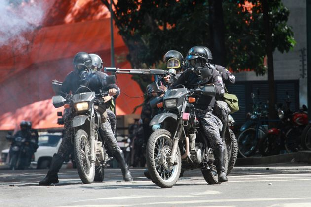 Riot police on their motorcycles charge on anti-government activists as they protest against the newly...