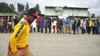 A man passes a long queue of voters outside a polling station in Kiserian, Kenya, on Tuesday, Aug. 8, 2017. The politicians are vying to lead a country that ranks among the five biggest economies in sub-Saharan Africa, is the worlds biggest exporter of black tea, and is a regional hub for companies including Google Inc. and Coca-Cola Co. Photographer: Riccardo Gangale/Bloomberg via Getty Images