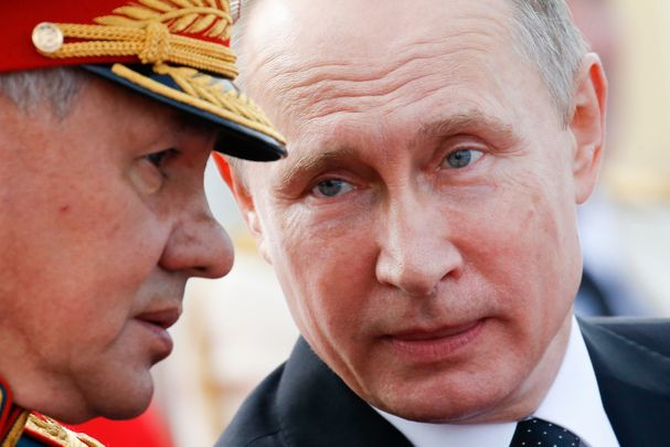 Russian President Vladimir Putin (R) speaks with Defence Minister Sergei Shoigu as they attend a ceremony for Russia's Navy Day in Saint Petersburg on July 30, 2017. President Vladimir Putin oversaw a pomp-filled display of Russia's naval might as the Kremlin paraded its sea power from the Baltic Sea to the shores of Syria.  Some 50 warships and submarines were on show along the Neva River and in the Gulf of Finland off the country's second city of Saint Petersburg after Putin ordered the navy to hold its first ever parade on such a grand scale.  / AFP PHOTO / POOL / Alexander Zemlianichenko        (Photo credit should read ALEXANDER ZEMLIANICHENKO/AFP/Getty Images)