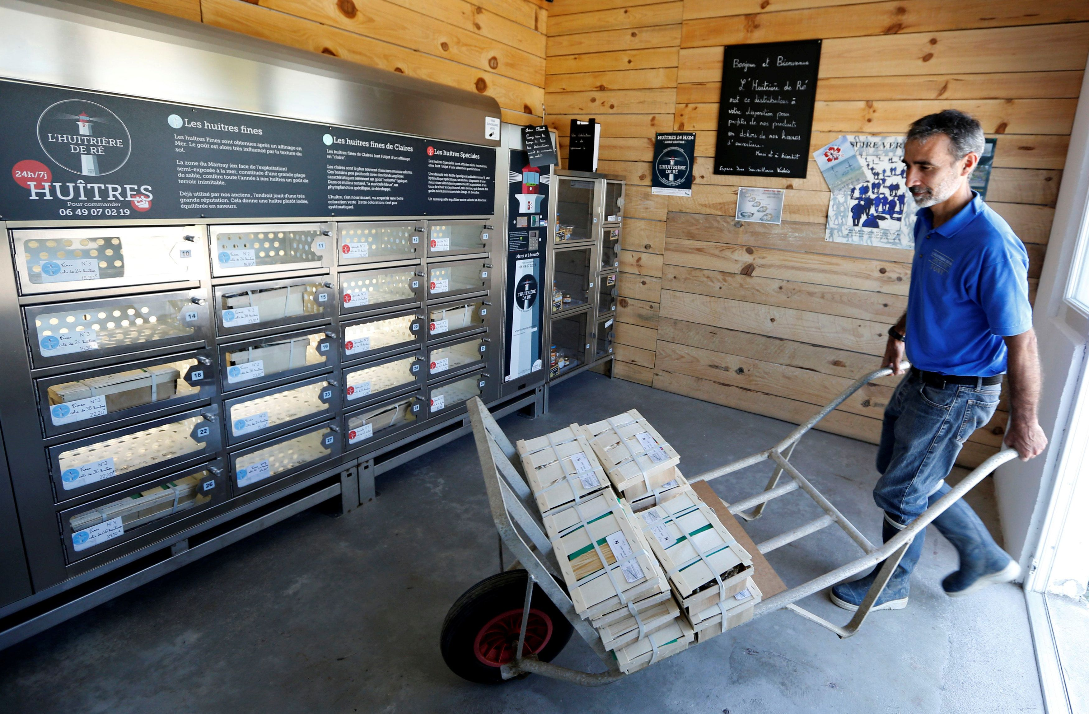 Tony Berthelot arrives with oysters at l'huitriere de Re, where the automatic oyster vending machine is set, in France on Aug