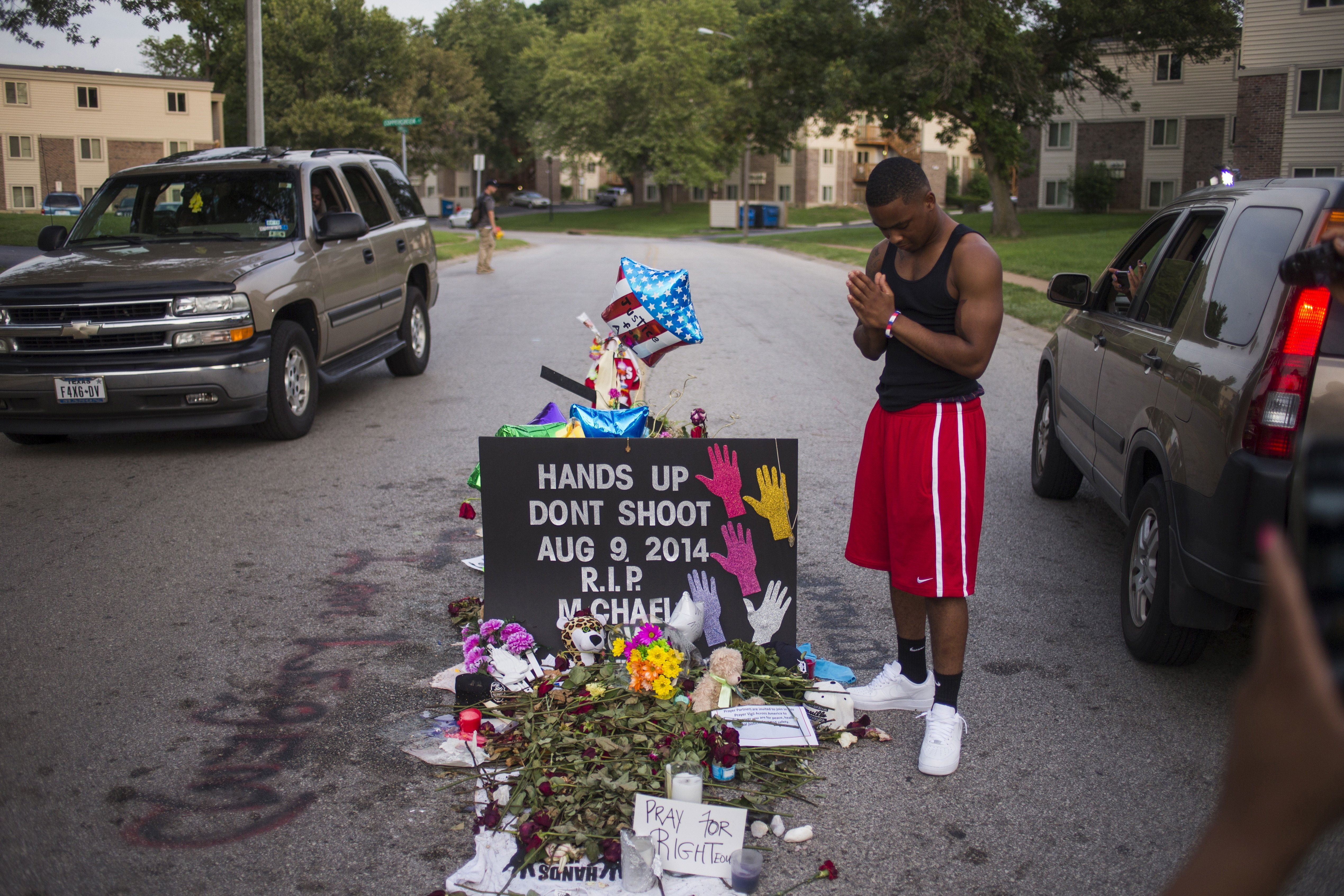 Local resident Ken Kendricks Jr. puts his hands together in prayer at a makeshift memorial at the site along Canfield Road where unarmed teen Michael Brown was shot dead in Ferguson, Missouri, August 22, 2014.   REUTERS/Adrees Latif/Files TPX IMAGES OF THE DAY