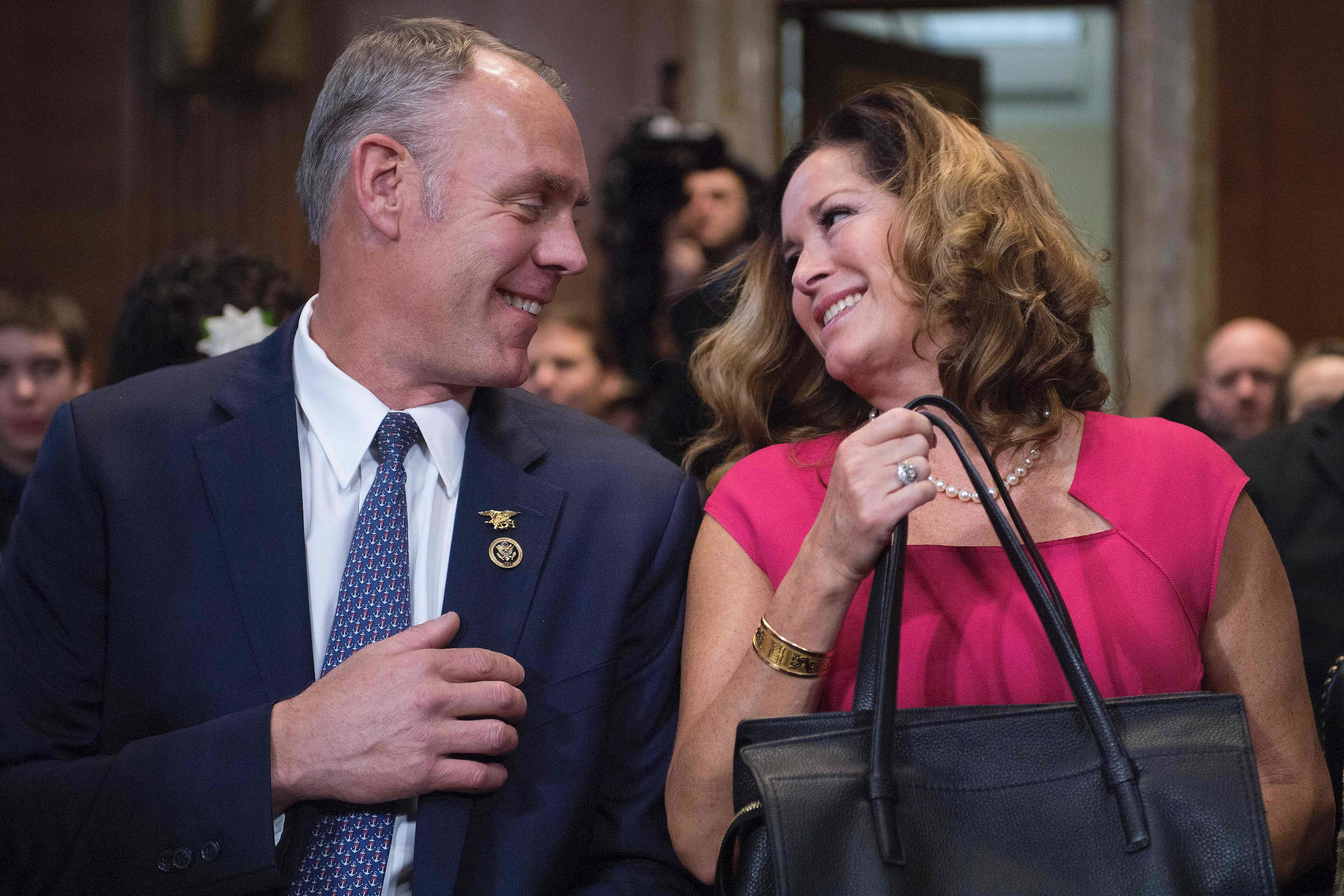 US Congressman Ryan Zinke (L), R-Montana, smiles at his wife Lolita Hand (R) as he prepares to testify before Senate Committee on Energy and Natural Resources on Capitol Hill in Washington, DC, January 17, 2017, on his nomination to be Secretary of the Interior in the Trump administration. / AFP / JIM WATSON        (Photo credit should read JIM WATSON/AFP/Getty Images)