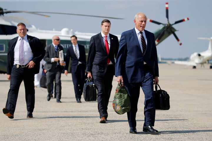 White House chief of staff John Kelly (right) walks with fellow staff to board Air Force One on Aug. 4, 2017.