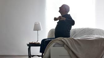 Senior man sitting on bed stretching his arms - Morning exercises