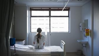 Patient sitting on hospital bed waiting for surgery looking out window