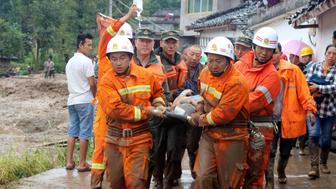 Rescue workers carry an injured villager at the site of a landslide that occurred in Gengdi village, Puge county, Sichuan province, China August 8, 2017. REUTERS/Stringer ATTENTION EDITORS - THIS IMAGE WAS PROVIDED BY A THIRD PARTY. CHINA OUT. NO COMMERCIAL OR EDITORIAL SALES IN CHINA.