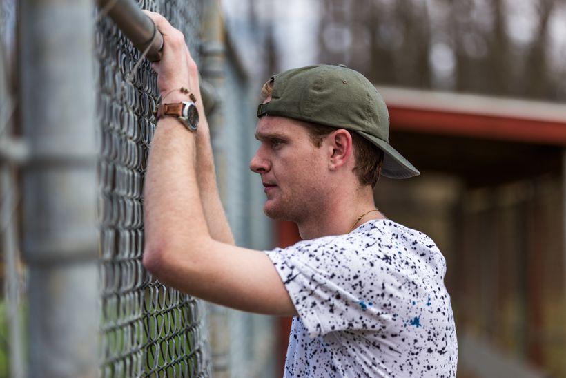 Washington, DC based rapper Garrett Zoukis reflecting at a baseball field.