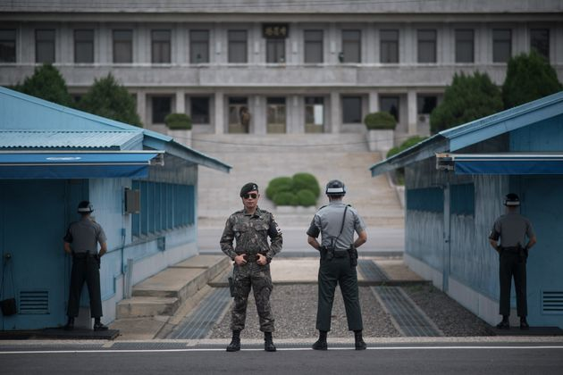 South Korean soldiers stand guard before North Korea's Panmon Hall (rear C) and the military demarcation...