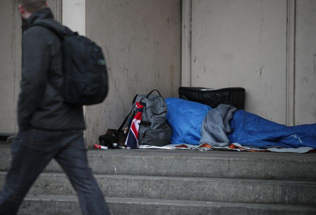 A homeless person sleeping rough in a doorway in