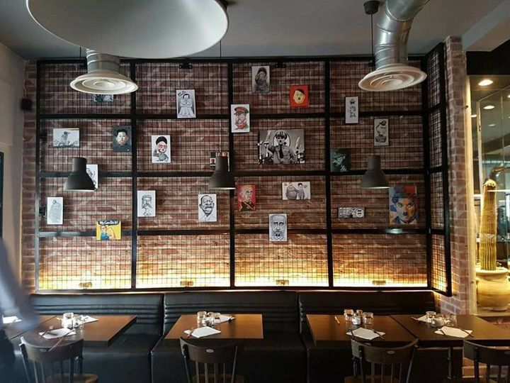 A wall of cartoon portraits in the Restaurant Le Dictateur.
