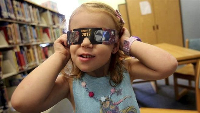 "Emmalyn Johnson, 3, tries on her ""eclipse glasses"" at her local library in North Carolina. Millions of people are expected to"