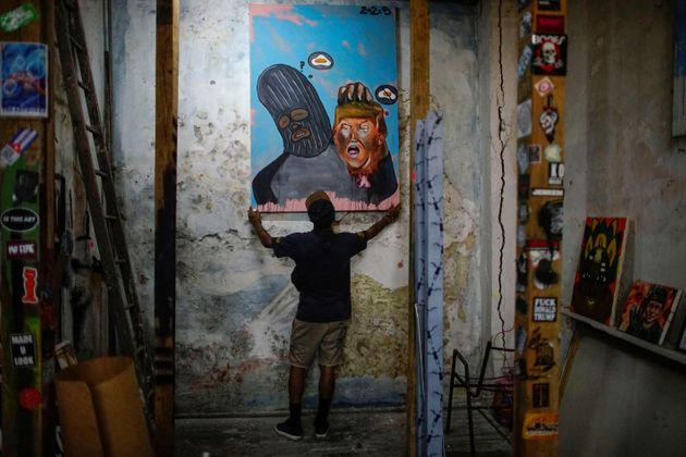Cuban artist Fabian Lopez shows one of his paints with his character holding Donald Trump's head in his...