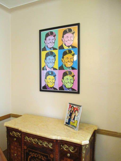 A Trump print and a framed copy of his People magazine cover.