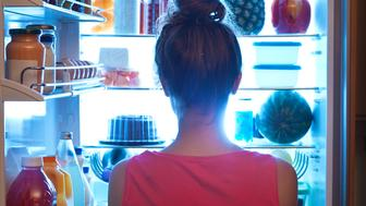 A young caucasian woman standing in front of the open refrigerator at late night, contemplating and wondering about a midnight snack in a domestic home kitchen. She is dressed in a bath robe hungry and looking for food. A symbol of dieting lifestyle. Photographed in vertical format.