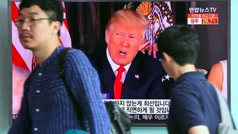 People walk past a television screen showing US President Donald Trump at a railway station in Seoul on August 9, 2017. President Donald Trump issued an apocalyptic warning to North Korea on Tuesday, saying it faces 'fire and fury' over its missile program, after US media reported Pyongyang has successfully miniaturized a nuclear warhead. / AFP PHOTO / JUNG Yeon-Je        (Photo credit should read JUNG YEON-JE/AFP/Getty Images)